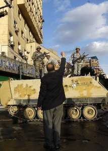 A protester raises his fist in front of an army armoured personnel carrier in Cairo's Tahrir Square