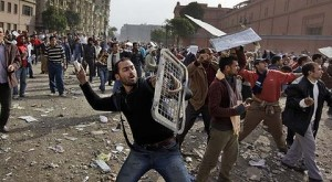 Anti-Mubarak protesters throw stones at the Tahrir Square, Cairo