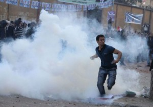 A Egyptian man throws back a teargas canister fired by policemen (AFP)